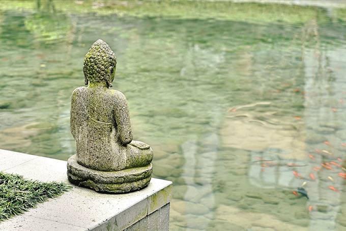 Buddha statue by pond