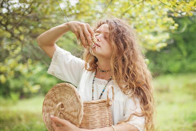uma jovem cheirando folhas