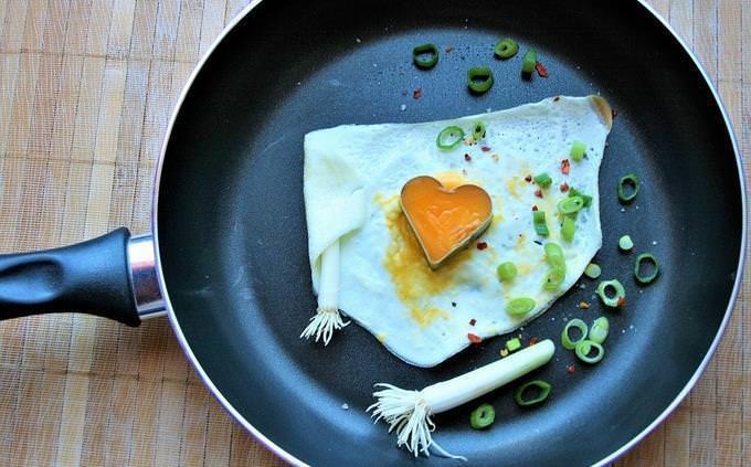 Ovo frito em uma panela com um cortador em forma de coração sobre ele
