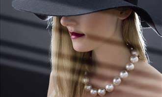mulher usando pérolas e um chapéu
