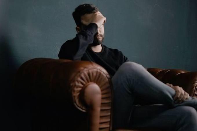 um homem com a mão na cabeça pensando