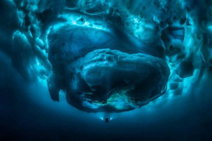 Um mergulhador comparado ao tamanho da parte submersade um iceberg.